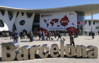 People walk next to the Mobile World Congress banner in Barcelona March 5, 2015. Ninety thousand executives, marketers and reporters gathered in Barcelona this week for the telecom operators Mobile World Congress, the largest annual trade show for the global wireless industry. REUTERS/Albert Gea (SPAIN - Tags: BUSINESS SCIENCE TECHNOLOGY TELECOMS) - RTR4S88M